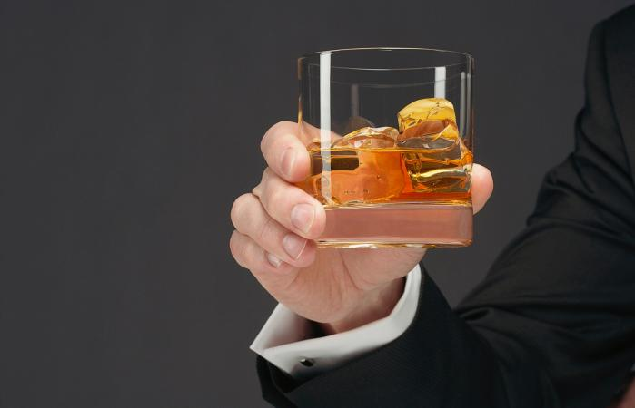 Man holding tumbler of scotch