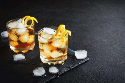 Whiskey on rocks with lemon twist on black stone background