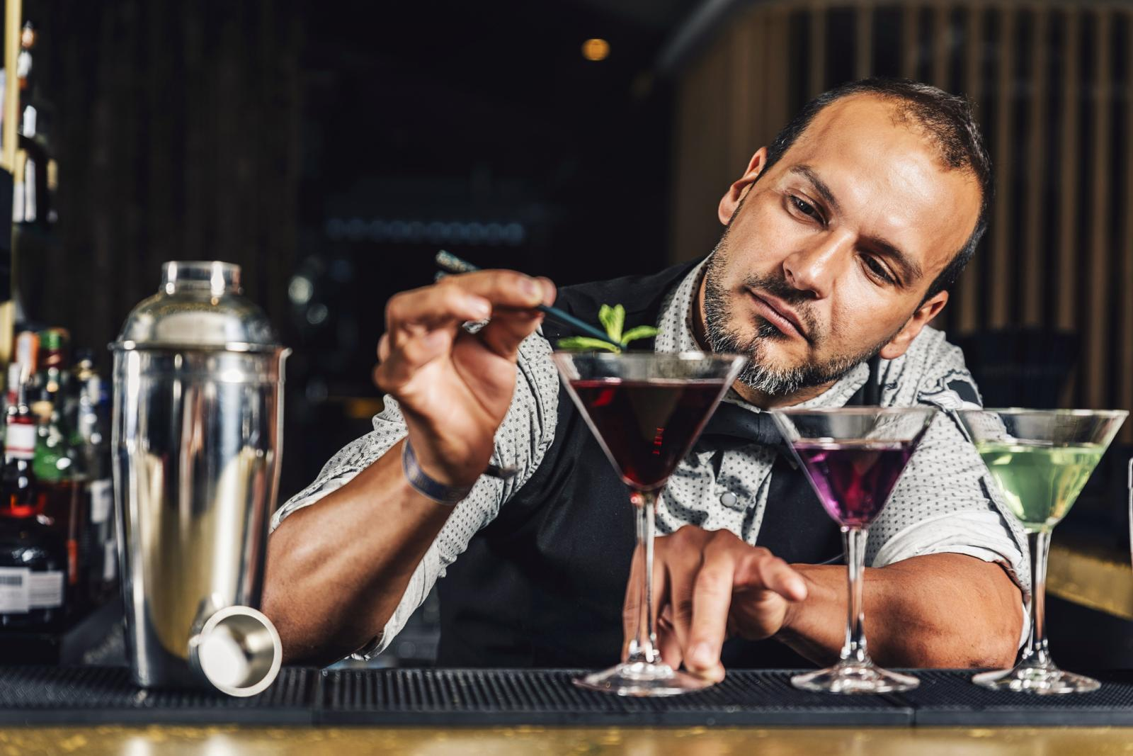 Bartender Garnishing Drink On Counter In Bar