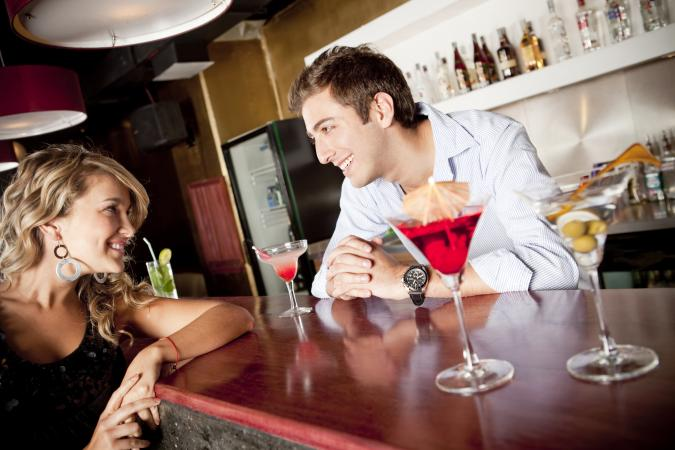 Woman drinking cocktail at bar talking to bartender