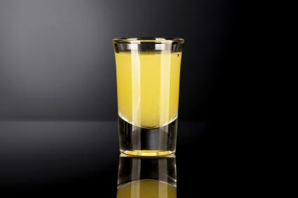 Shot glass with alcohol on a dark background