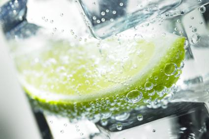 A slice of lime with ice in a sparkling drink