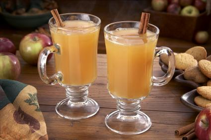 Steaming hot cider on a table with apples and ginger cookies