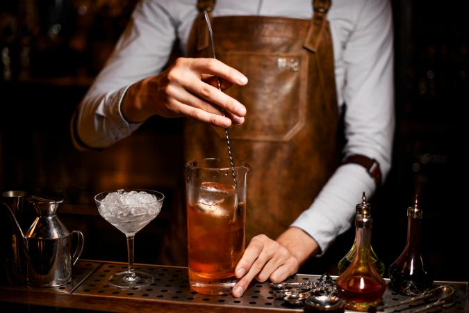 Bartender stirs alcohol drink with a spoon
