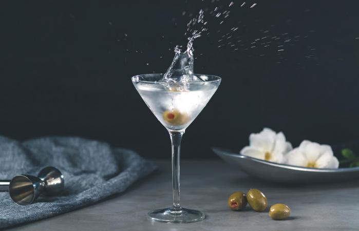 Olive falling in vodka martini