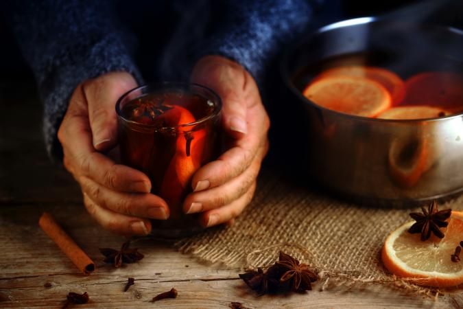 Older female hands holding a glass mug with hot mulled wine