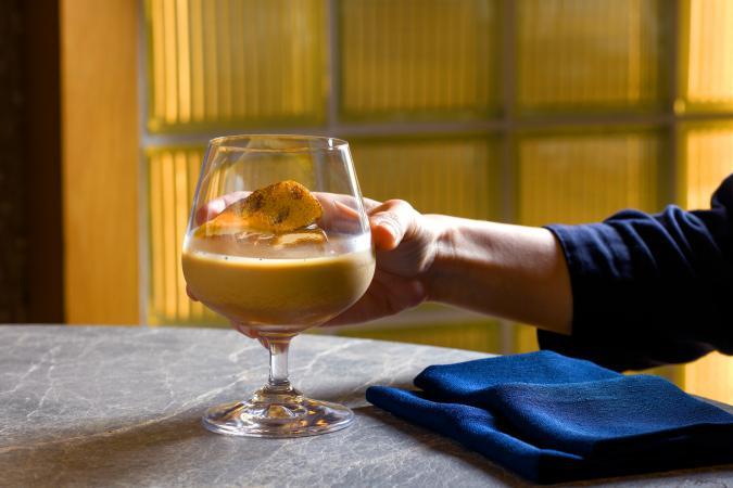 A hand holding a Baileys cocktail glass