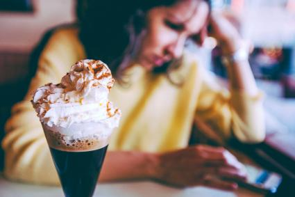 Irish coffee and woman sending phone message in the background