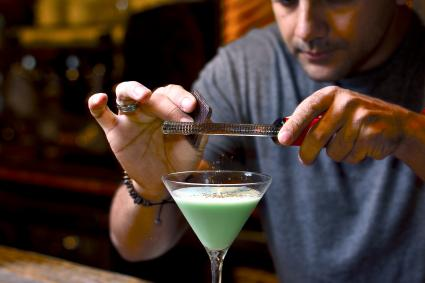 Bartender grating chocolate on the mint cocktail