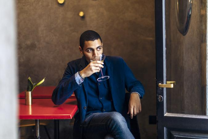 Young man relaxing at a bar with an after work cocktail