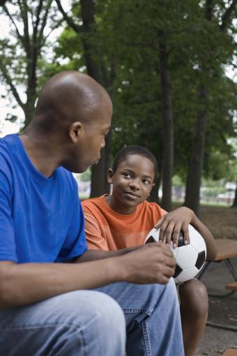Man and boy sitting with soccer ball