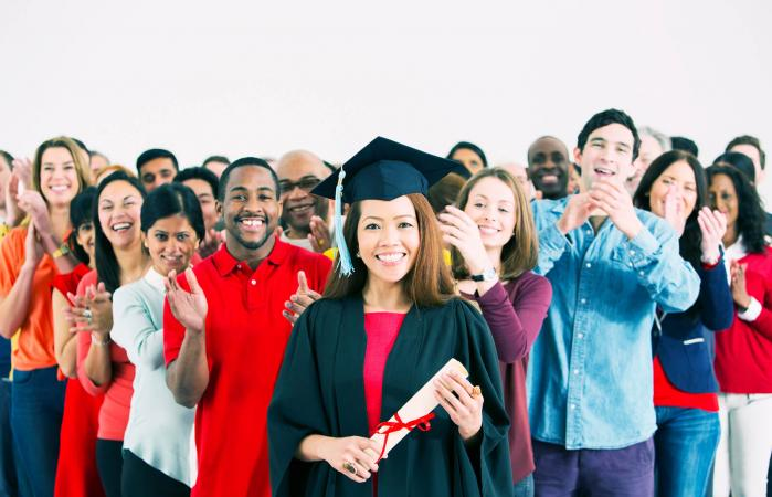Crowd clapping behind happy graduate