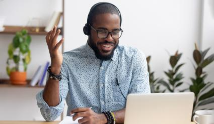 Smiling African American employee in headphones using laptop