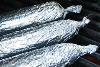 Foil-wrapped corn on the grill; © Lschirmbeck | Dreamstime.com
