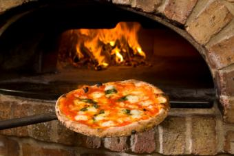 putting pizza in brick oven
