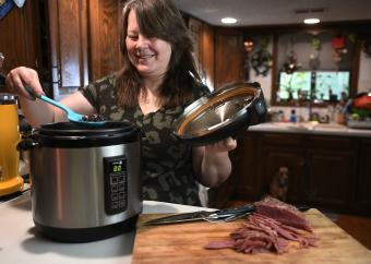 Woman using electric pressure cooker