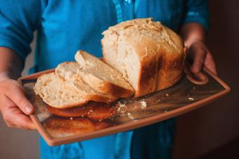 Hands holding tray of fresh bread
