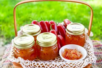 Red Jalapeno peppers with fresh jars of peach jalapeno jelly