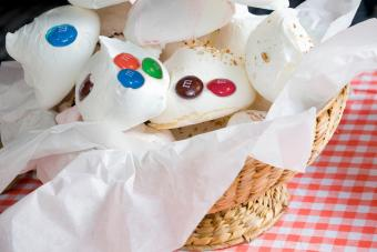 White meringues in wicker basket on red gingham kitchen table cloth