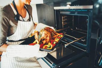 woman taking the turkey out of the oven