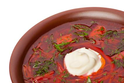 Borscht topped with sour cream and parsley