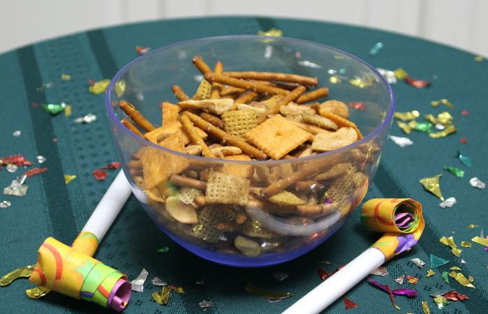 Bowl of Chex party mix and party blowers