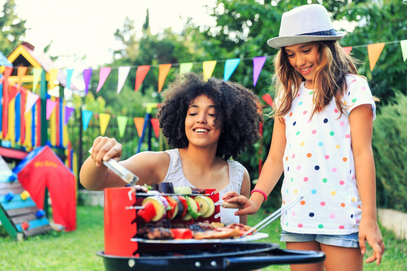 Mother and daughter having fun and preparing barbecue at backyard