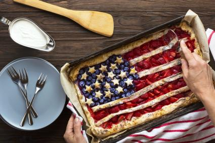 Woman cuts a berry pie in the form of an American flag