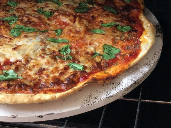 Pizza on pizza stone cooking on grill