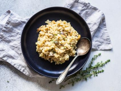 Italian risotto with porcini mushrooms and fresh thyme in a black plate on a grey background