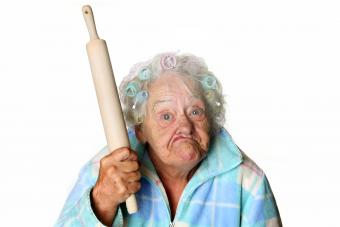 Cranky granny making faces and holding rolling pin