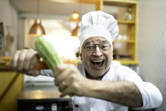 Man dresses as chef while holding a cucumber and a carrot