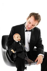 Man in a ventriloquist costume with a dummy