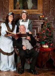 Three people in Victorian costume caroling