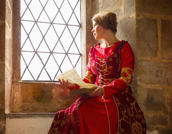 Woman in medieval costume reading at castle window