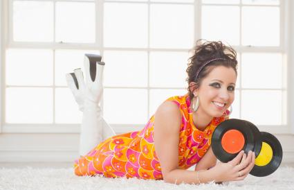 woman in nostalgic dress holding vinyl records