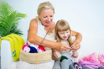 Grandmother knitting with granddaughter