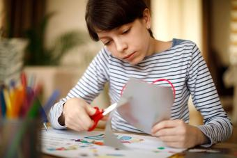 Girl cutting paper for craft project