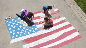 Girls with chalk coloring American flag on sidewalk