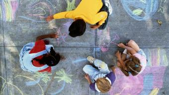 Four children drawing with chalk on pavement