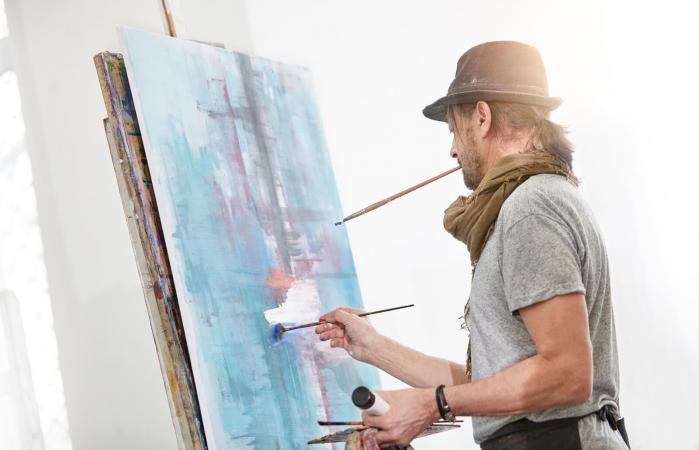 Male artist painting at easel