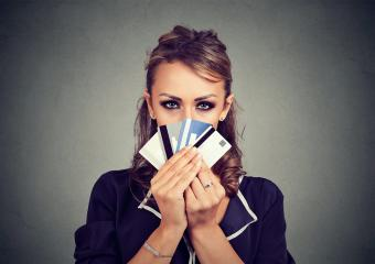 Woman hiding face behind many credit cards
