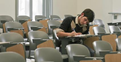 Male college student working in classroom