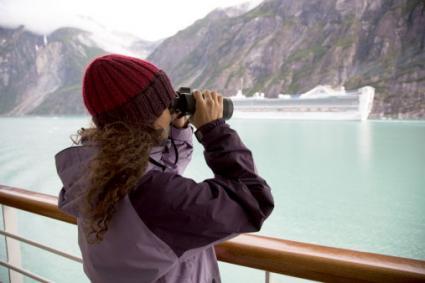Woman using binoculars on Alaskan cruise ship