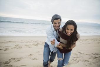 Playful couple hugging on beach
