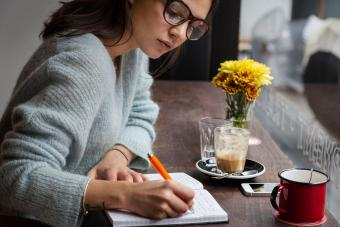 Woman writing in notebook in cafe