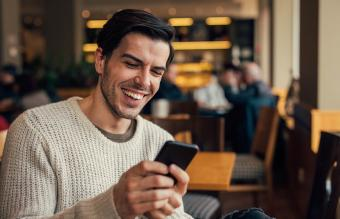 man laughing reading text message on phone