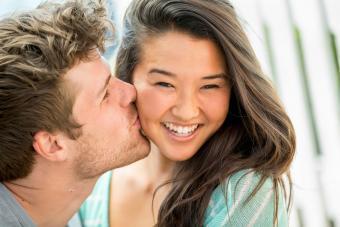 Man kissing girlfriends cheek