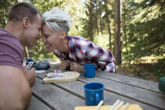 Happy couple playing cribbage at campsite
