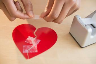 woman taping broken paper heart